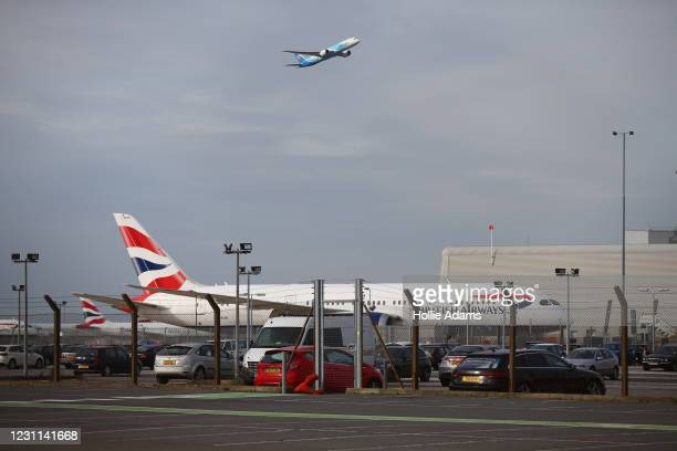 Plane takes off in view of a British Airways aeroplane at Heathrow Airport on February 13, 2021 in London, England. From 15 February travellers to...