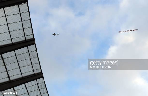 TOPSHOT A plane towing a banner reading 'White Lives Matter Burnley' is seen in the sky above the stadium during the English Premier League football...
