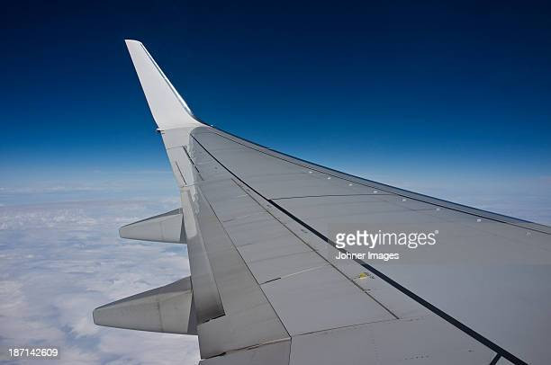 Plane wing against blue sky