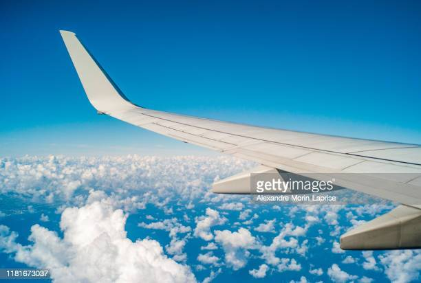 plane wing during flight over united states with blue sky and small white clouds - aircraft wing stock pictures, royalty-free photos & images
