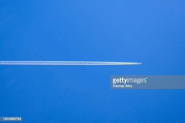 plane with contrails - trainée d'avion photos et images de collection