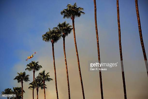 A plane works to control wildfires as they burn through hillsides on January 16 2014 in Azusa California Authorities have stated that three people...