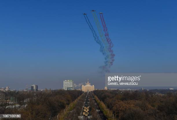 Planes spread the colors of the national flag in the sky as they fly over the military parade on Romania's National Day in Bucharest December 1 2018...