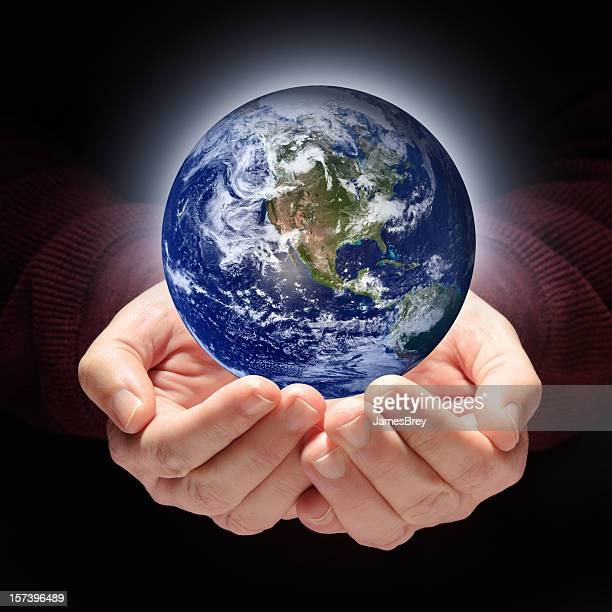 planet earth held in nurturing, protecting hands - earth day stock pictures, royalty-free photos & images