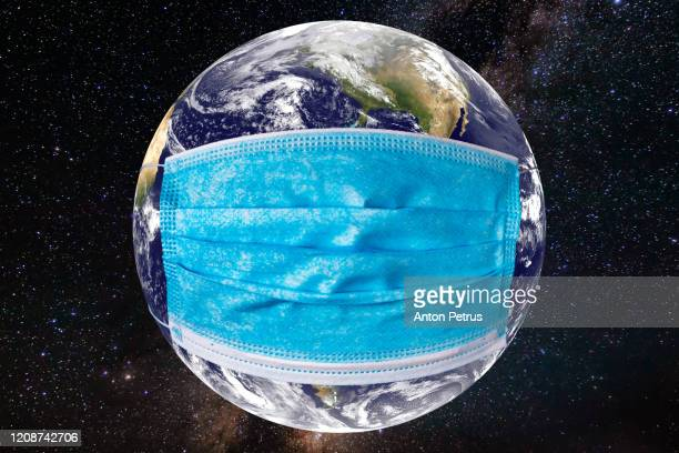 planet earth with a medical mask. world epidemic concept - prevention imagens e fotografias de stock