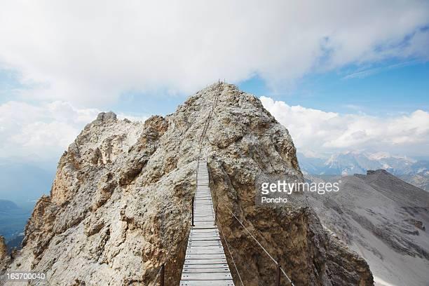 plank bridge between mountain peaks