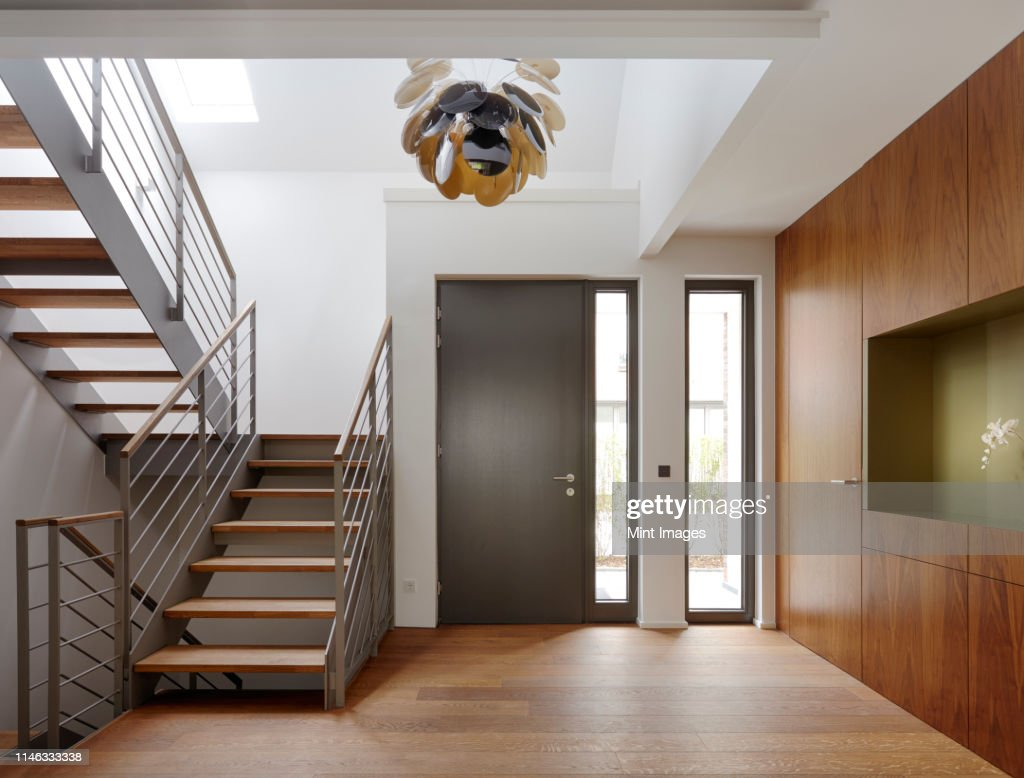 Plank floor and walnut wall covering in home near staircase : Stock Photo