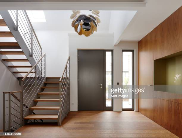 plank floor and walnut wall covering in home near staircase - front door stock pictures, royalty-free photos & images