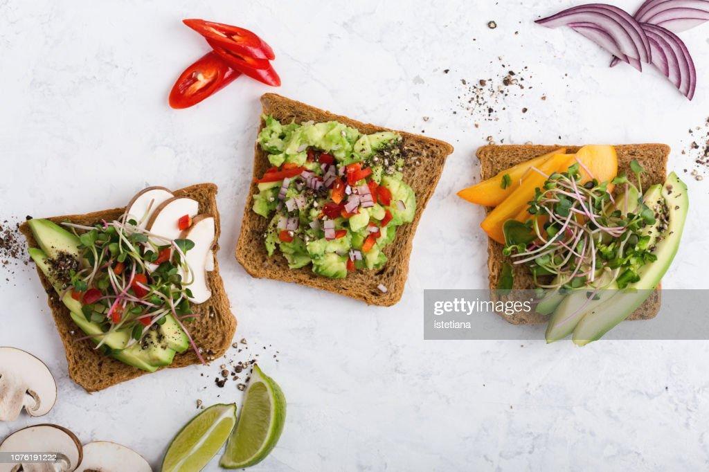Plant based colorful vegan snack, variety of avocado toasts : Stockfoto