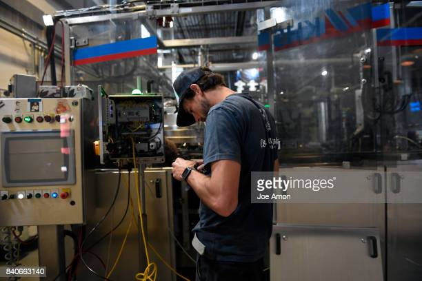 Plant manager Brian Shaeffer of the Oskar Blues staff setting up a Liquid Nitrogen Doser that will firm up the cans as the company has halted beer...