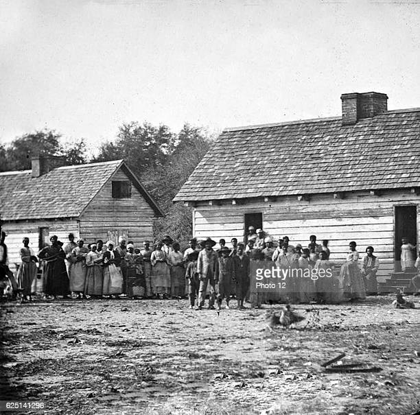 Plantation slaves gathered outdside their huts, Virginia.