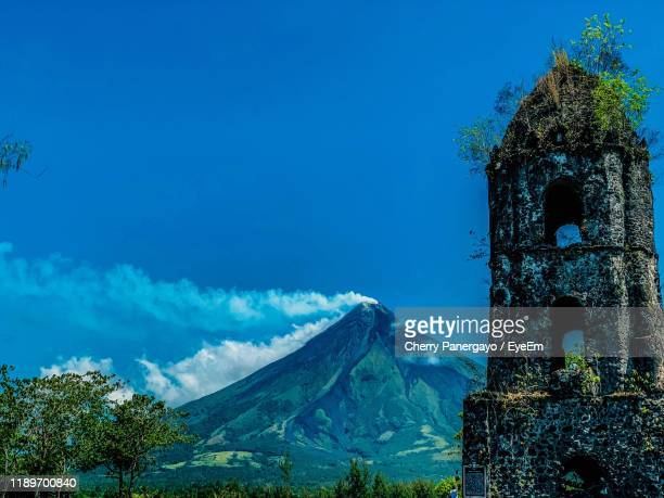 plants by old building against blue sky - philippines stock pictures, royalty-free photos & images