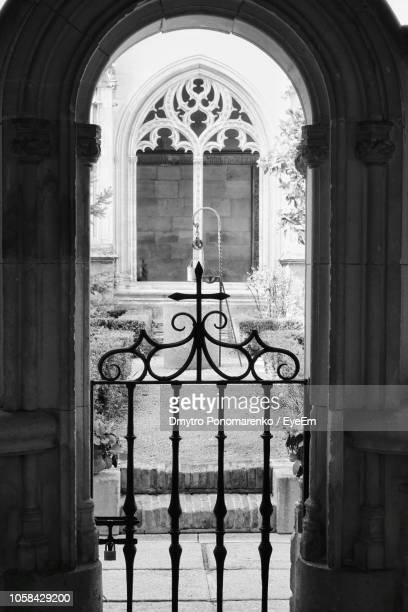 plants in courtyard seen through church arch - arch stock pictures, royalty-free photos & images