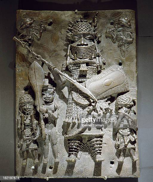 Plaque which decorated the palace of the Benin Obas, Decorated with a figure of an Oba with ceremonial dress and weapons. Nigeria. Possibly late 16th...