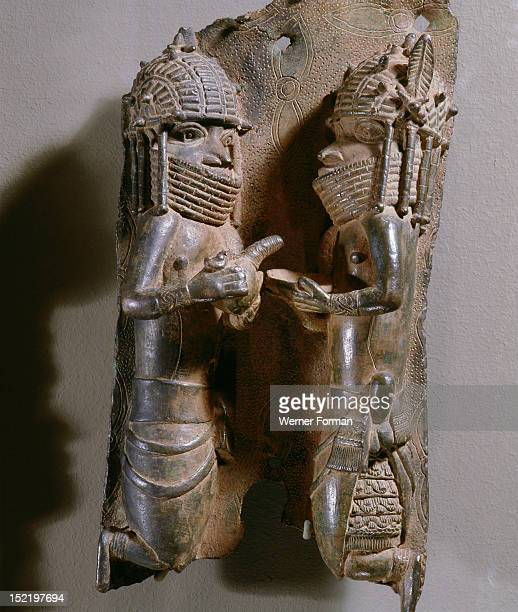 Plaque which decorated the palace of the Obas of Benin, Retainers of the Oba are depicted pouring liquid from a calabash container. Nigeria. Edo....