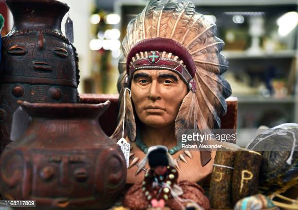 Plaster bust of an American Indian chief wearing a feather headdress or war bonnet is among items for sale in an antiques shop in Grants Pass, Oregon.
