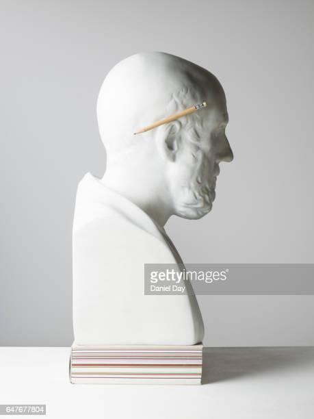 Plaster cast of a man with pencil and glasses