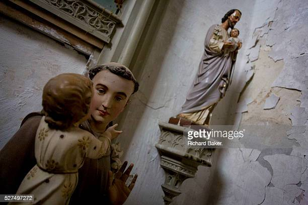 Plaster Catholic idols in a corner of the SaintGervaisSaintProtais church at Le GrandPressigny IndreetLoire France In the foreground is a small child...