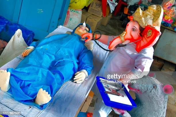 Plasters of Paris idols depicting the present pandemic scenario where Hindu God Ganesh is treating a patient from coronavirus COVID-19 disease, ahead...