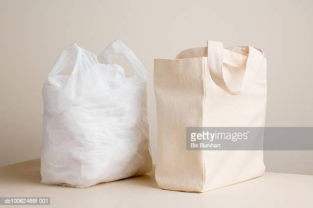 Plastic bag and canvas bag on table