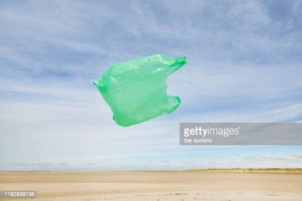 plastic bag flying in the wind on the beach against sky - ビニール袋 ストックフォトと画像
