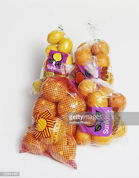Plastic bags of citrus fruits on white background, close-up