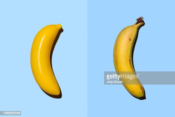plastic banana beside real banana - side by side stock pictures, royalty-free photos & images