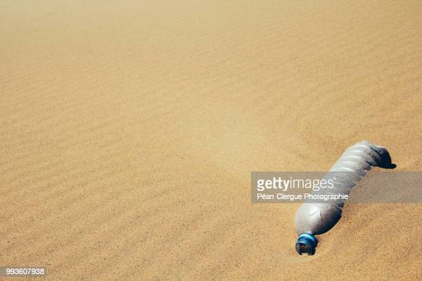 Plastic bottle buried in sand, Morocco