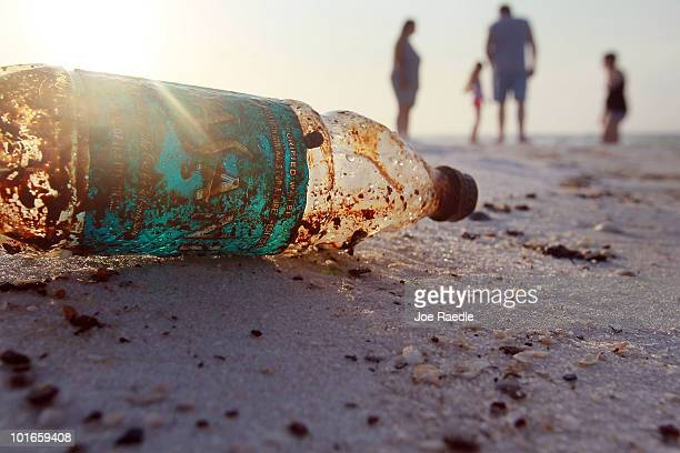 A plastic bottle is seen coated in oil on Pensacola Beach as oil makes its way on shore from the Deepwater Horizon oil spill in the Gulf of Mexico on...