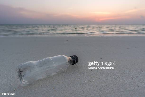 Plastic bottle on an empty beach at sunset