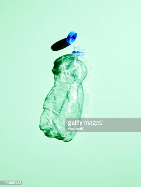 plastic bottle on green background - plastikmaterial stock-fotos und bilder