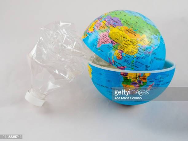 a plastic bottle on planet earth. plastic pollution concept - ease stock pictures, royalty-free photos & images