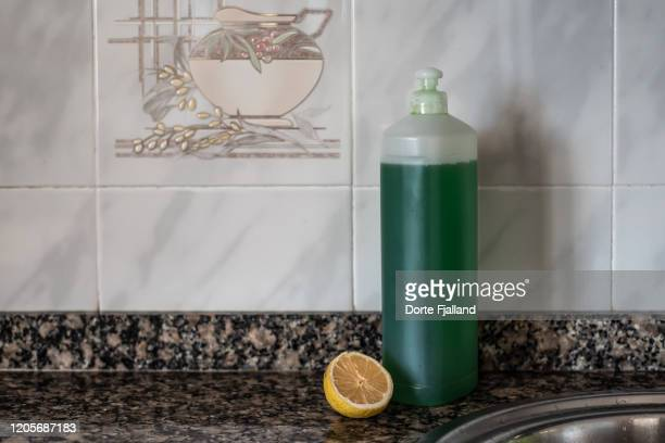 plastic bottle with green dishwashing soap and half a lemon on a terrazzo kitchen counter - dorte fjalland imagens e fotografias de stock