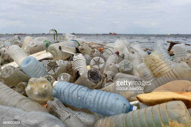Plastic bottles and other waste cover a beach after being washed ashore near the port of Abidjan on August 5 2015 despite efforts by the government...