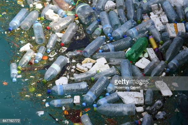 plastic bottles and polystyrene floating in sea. - plastic stockfoto's en -beelden