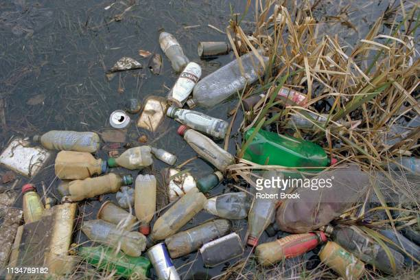 plastic bottles in polluted waterway - water pollution stock pictures, royalty-free photos & images