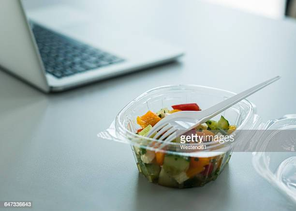 Plastic bowl with salad on desk in office