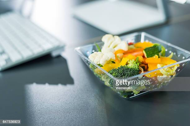 Plastic bowl with vegetables on desk in office
