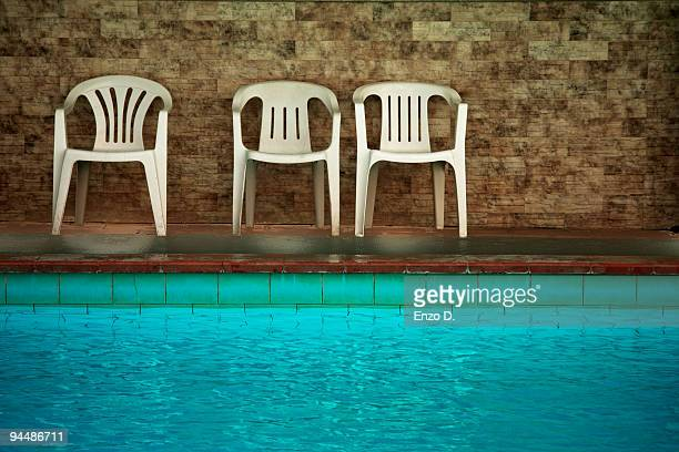 Plastic chairs next to a pool