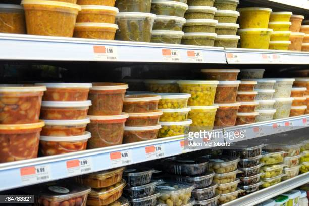 Plastic containers of food on supermarket shelves