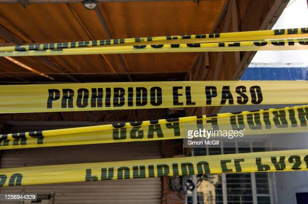plastic cordon tape stating in spanish 'prohibido el paso' [no entry/no trespassing] across a building front - cordon tape stock pictures, royalty-free photos & images