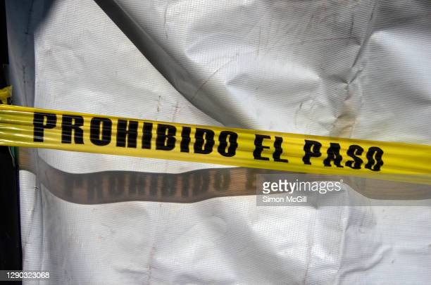 plastic cordon tape stating in spanish 'prohibido el paso' [no entry/no trespassing] across a white tarpaulin - cordon tape stock pictures, royalty-free photos & images
