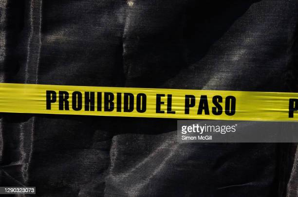 plastic cordon tape stating in spanish 'prohibido el paso' [no entry/no trespassing] across a black tarpaulin - cordon tape stock pictures, royalty-free photos & images