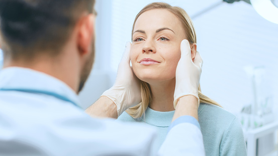 Plastic / Cosmetic Surgeon Examines Beautiful Woman's Face, Touches it with Gloved Hands, Inspecting Healed Face after Plastic Surgery with Amazing Results. 1043634348