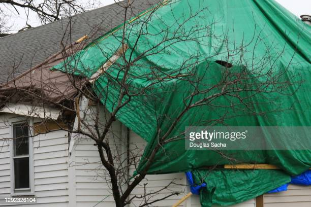 plastic cover on a house protecting from it after the storm - tarpaulin stock pictures, royalty-free photos & images