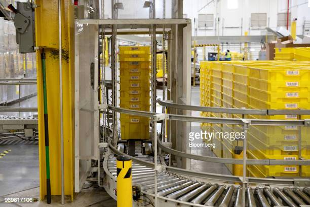 Plastic crates move along a conveyor at the Amazoncom Inc fulfillment center in Robbinsville New Jersey US on Thursday June 7 2018 Seattlebased...