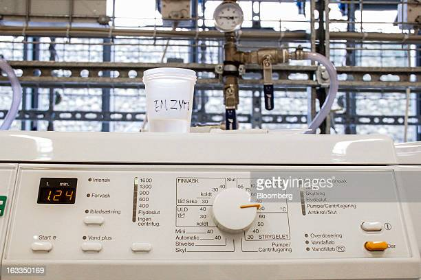 A plastic cup labelled 'enzymes' stands on a washing machine used for testing cleaning enzymes used in detergents at the headquarters of Novozymes...