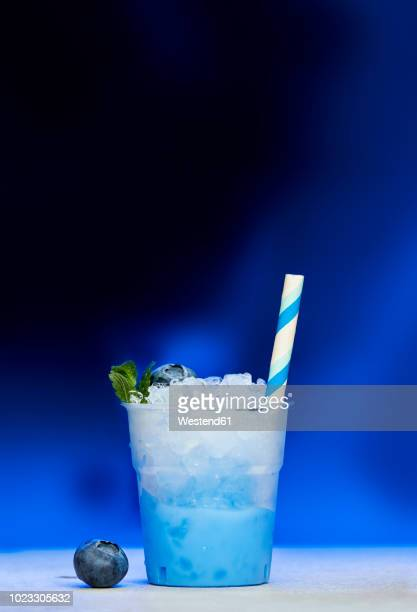plastic cup of blueberry slush - slush stock photos and pictures
