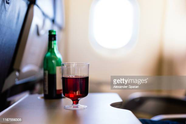 plastic cup of red wine in the airplane - alcohol stock pictures, royalty-free photos & images