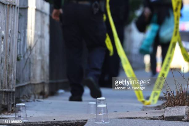 Plastic cups cover empty bullet shell casings at the scene of a shooting that left multiple people injured in the Flatbush neighborhood of the...